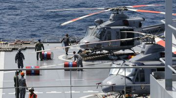Crew members roll fuel barrels as they prepare helicopters for flights on the deck of Indonesian Navy ship KRI Banda Aceh. (AAP)