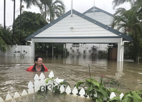 Townsville resident Amelia Rankin almost up to her shoulders in floodwaters at her home.