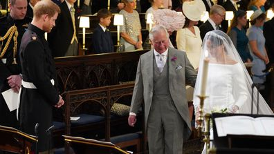 Britain's Prince Harry looks at his bride, Meghan Markle, as she arrives accompanied by the Prince Charles during the wedding ceremony of Prince Harry and Meghan Markle at St. George's Chapel in Windsor Castle in Windsor, near London, England, Saturday, May 19, 2018
