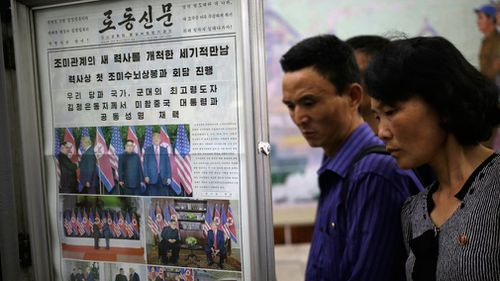 People read newspapers fronting the US President Donald Trump's summit with North Korean leader Kim Jong Un at the Puhung subway station in Pyongyang. Picture: AAP