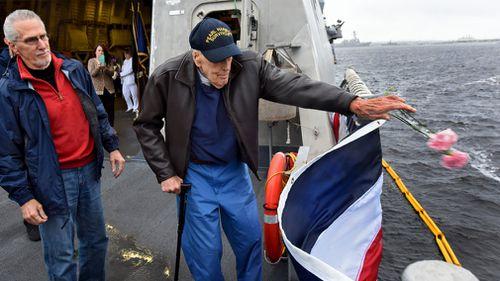 Pearl Harbor survivor Robert Beaudreau, 98, tosses flowers into the sea. (AAP)