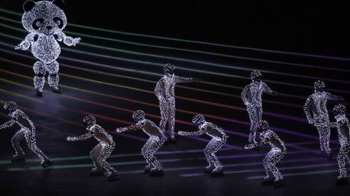 Popular K-pop band EXO performed and volunteers made their way into the stadium wearing hats with the Olympic tiger mascot on them, dancing around the athletes. (AAP)