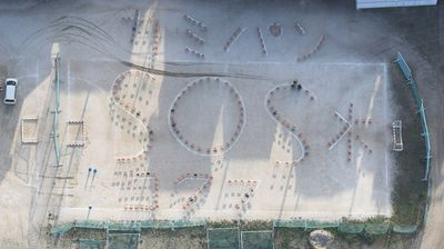 Staff and students at Kumamoto Kokubu High spelled out a plea for help with chairs. The message requests water and paper.