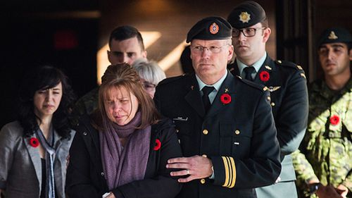 Cirillo's mother supported by military personnel.