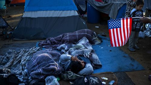 A migrant holding a US flag, right, speaks with others waking up at the Benito Juarez Sports Center that's serving as a temporary shelter in Tijuana, Mexico, November 26.