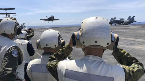 An American aircraft carrier has sailed through the South China sea, as China continued to show off its military might.