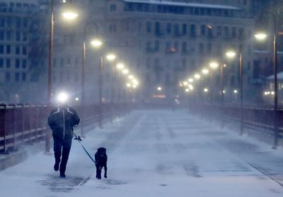 A runner and his dog brave frigid conditions while making their way east across the Stone Arch Bridge in Minneapolis.