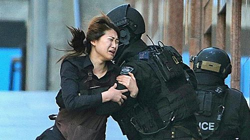 Jieun Bae runs to armed tactical response police officers for safety after she escaped from a cafe under siege at Martin Place in the central business district of Sydney, Australia. (Rob Griffith)
