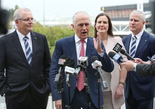 Prime Minister Malcolm Turnbull (centre) speaks to the media as Treasurer Scott Morrison (left) and Michael McCormack (right) look on during a press conference at Melbourne. (AAP)
