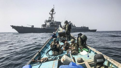 Search and seizure team from the guided-missile destroyer USS Jason Dunham (DDG 109) inspects a dhow while conducting maritime security operations. (AP)