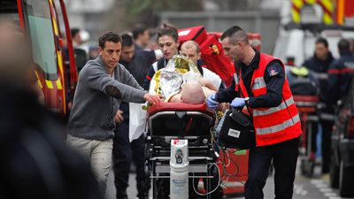 A man believed to be one of the 10 people injured in the attack is transferred to an ambulance.<br><br>Twelve others were killed in the shooting at French satirical magazine Charlie Hebdo. (AAP)
