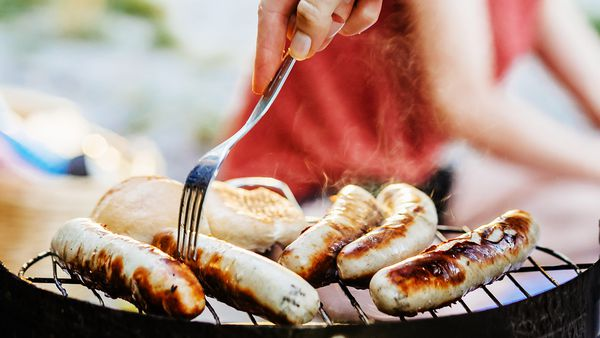A close up of sausages being cooked on a barbecue by the lake.