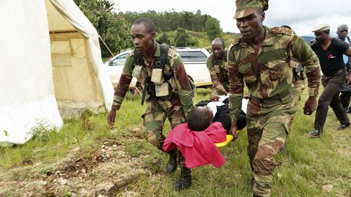 Soldiers carry wounded people to medical treatment tents.