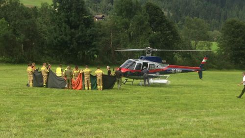Rescuers stand next to a police helicopter in Krimml in the Austrian province of Salzburg. (AP)