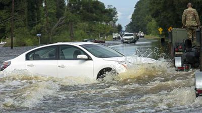 An abandoned vehicle is surrounded by water on Highway 190 near Holden, Louisiana. (AP)