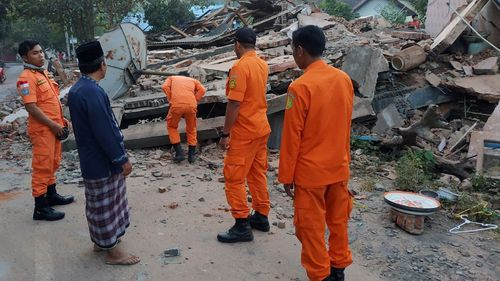 Rescuers inspecting collapsed houses after the earthquake struck in Bali and Lombok.