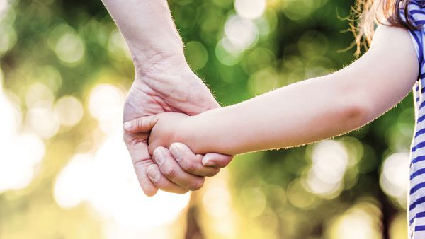 Dad holding daughter's hand