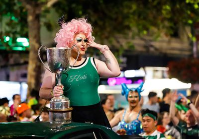 A drag green dressed in a pine green top and a cotton-candy pink wig shows off her trophy. (AAP)