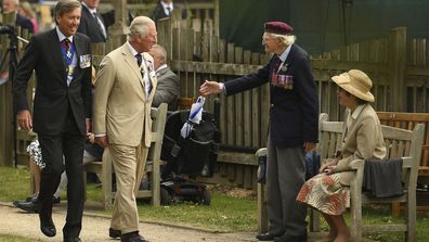 A veteran stands to greet Britain's Prince Charles as he arrives for the national service of remembrance marking the 75th anniversary of V-J Day at the National Memorial Arboretum in Alrewas, England, Saturday Aug. 15, 2020