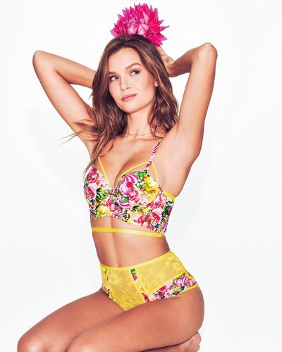 A Victoria's Secret model wears the yellow high-waist lingerie set from the <em>VS Loves Mary Katrantzou</em> collection.