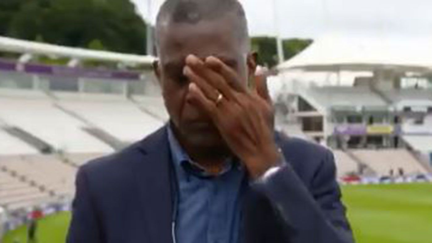 Michael Holding wipes away tears during a live interview discussing racism.