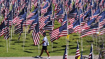 A pedestrian walks past a field of American flags, each representing every victim murdered in the terrorist attacks of Sept. 11, 2001, at the 9/11 Memorial Healing Field, in Tempe, Arizona.