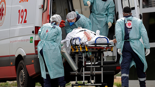 Healthcare workers receive a patient suspected of having COVID-19, from an ambulance at the public HRAN Hospital in Brasilia, Brazil, Thursday, March 11, 2021. (AP Photo/Eraldo Peres)