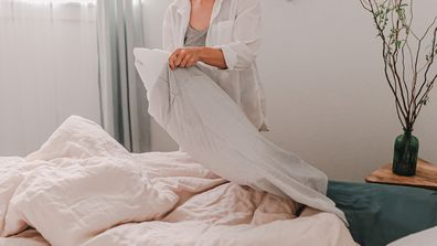 Woman making her bed changing pillowcase