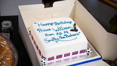 Prince William, Duke of Cambridge is presented with a birthday cake by shop owner Paul Brandon during a visit to Smiths the Bakers, in the High Street on June 19, 2020 in King's Lynn, Norfolk.