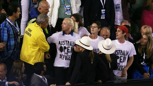 Demonstrators are removed from Rod Laver Arena after they protested for the closure of an offshore detention centre on Manus Island during the Australian Open final. (Getty Images)