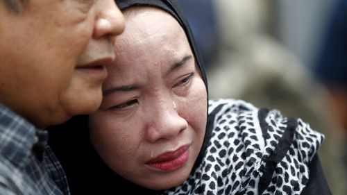 Family members cry outside the school where 24 people perished. (AAP)