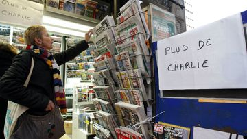 A women selects a newspaper, near to a notice reading, 'No more Charlie Hebdo' after all copies of the satirical newspaper were sold out. (AAP)