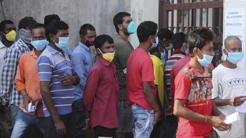 People wait in a queue to register their names to have their nasal swab samples taken to test for COVID-19 at a government hospital in Jammu, India.