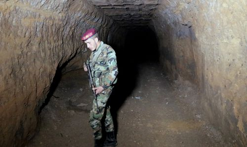 A Syrian soldier stands at one of the underground tunnels under the recently-captured Jobar town in the Eastern Ghouta, in the countryside of Damascus, Syria. (AAP)