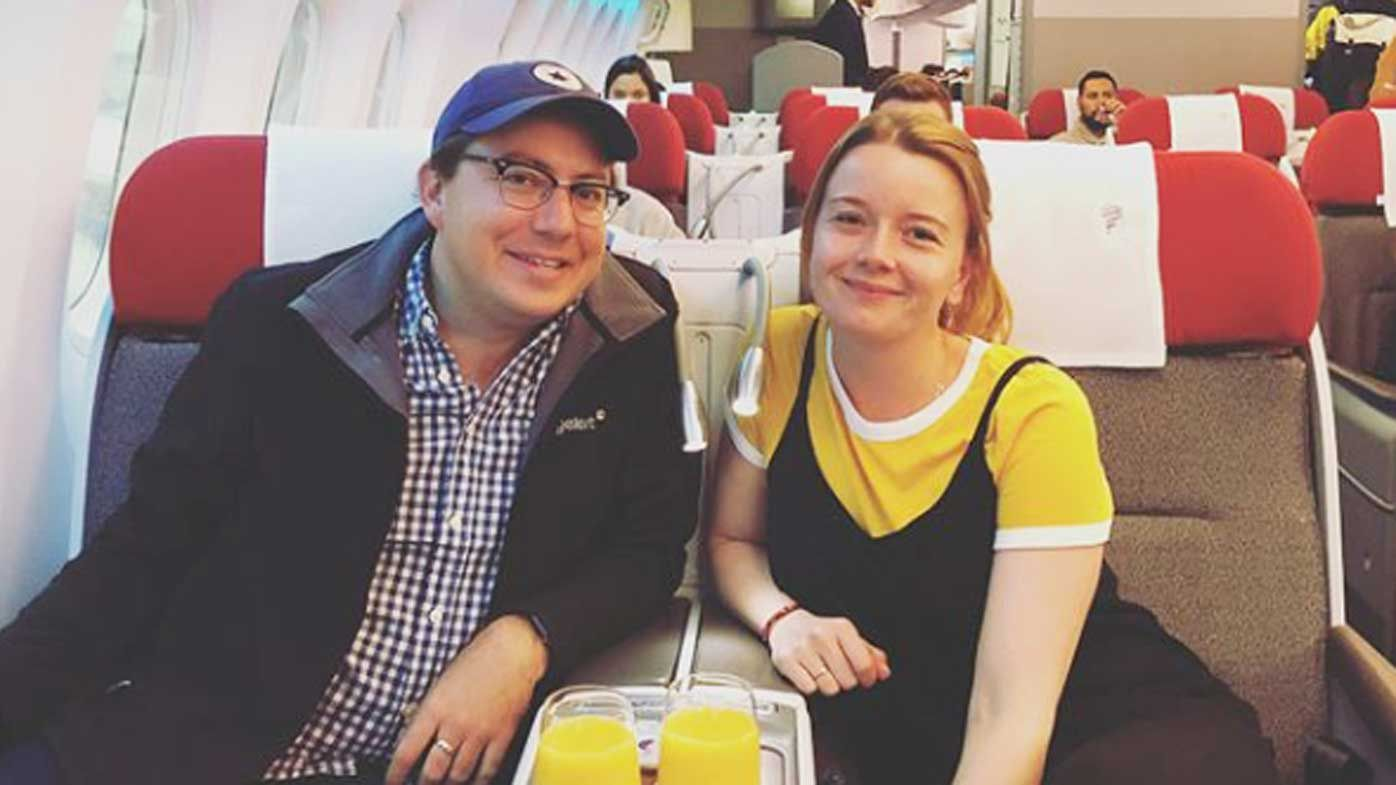 UK couple in business class sipping orange juice
