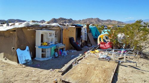 Three children – ages 11 to 14 – have been forced to live in a plywood box in the desert for several years without running water, bathrooms or electricity. (AAP/Morongo Basin Sheriff Station)