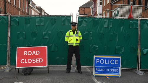 A police officer stands in front of screens erected in Rollestone Street, Salisbury, Wiltshire. Picture: AAP