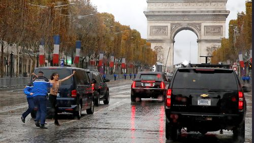 Topless protester runs at Donald Trump's motorcade on Champs Elysees