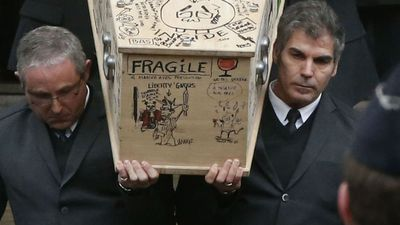 "Cartoons, including a ""Paradise Survival Kit"" and ""FRAGILE"" plastered Tignous' coffin as he was laid to rest. (AFP)"