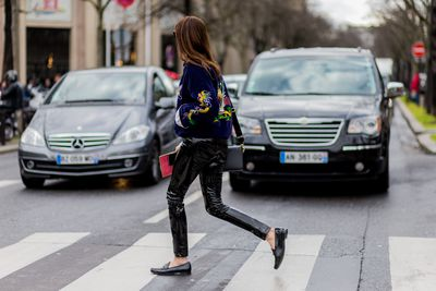 Ex-<em>Vogue</em> <em>Turkey</em> editor, Ece Sukan pairs her sporty, embroidered velvet bomber with slick, patent leather pants and loafers at Paris Fashion Week.