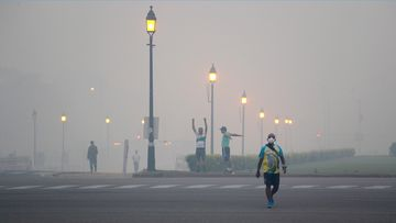Morning walkers exercise amidst smog due to firecrackers burnt in Thursday's Diwali festival, in New Delhi, India. (AP)
