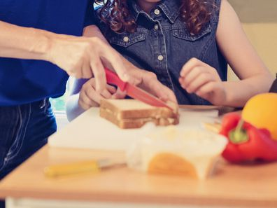 Mother and child cutting sandwich