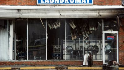 A burnt laundromat at the intersection of Chambers Road and West Florissant Avenue in Ferguson, Missouri. 61 people were arrested during the riots overnight. (AAP)