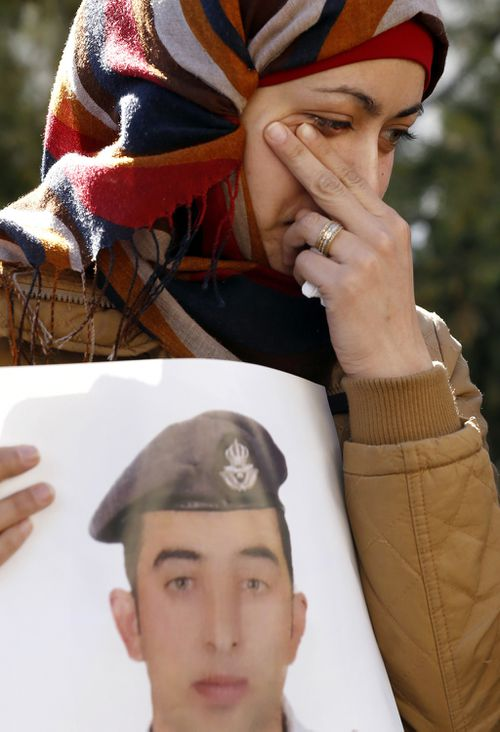 Anwar al-Tarawneh, the wife of the Jordanian pilot, holds a poster of him as she weeps during a protest. (AAP)