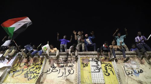 Sudanese protesters shout slogans from the top of a blocked rail road bridge at the site of a sit-in, near the Army headquarters, in Khartoum, Sudan.
