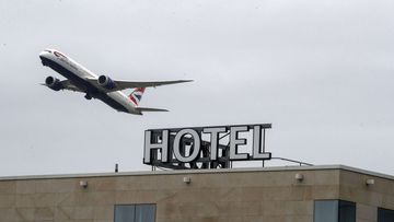 A plane passes over the Sofitel Hotel near London's Heathrow. Tuesday, Jan. 26, 2021.