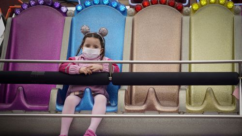 A young girl wearing a face mask rides a fairground attrtction on the Central Pier on October 16, 2020 in Blackpool, England. The Lancashire region will go into Tier 3 of Covid-19 lockdown restrictions from 00.01 Saturday 17th October.