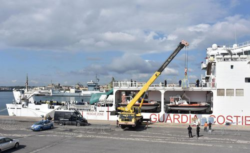 Water and other supplies are being loaded on the Italian Coast Guard ship Diciotti, where migrants waited permission to disembark, in the port of Catania, Italy