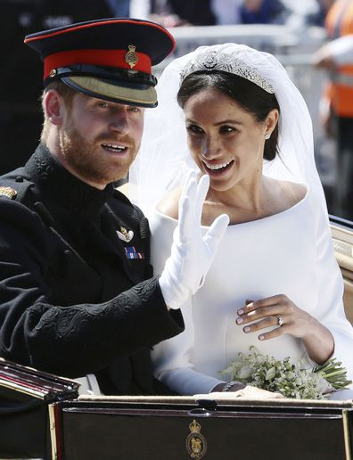 Meghan Markle reacts as she rides in a carriage with her husband Britain's Prince Harry after their wedding ceremony at St. George's Chapel in Windsor Castle in Windsor, near London, England, Saturday, May 19, 2018