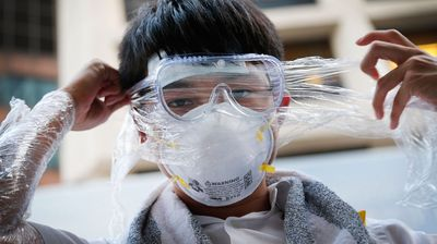A student pro-democracy protester covers his face in plastic wrap to protect against pepper spray.